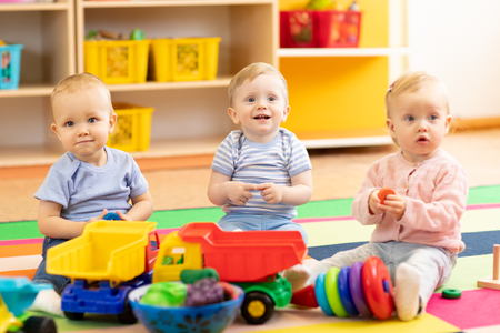 Babies playing together in the kindergarten, nursery or daycare Stock Photo