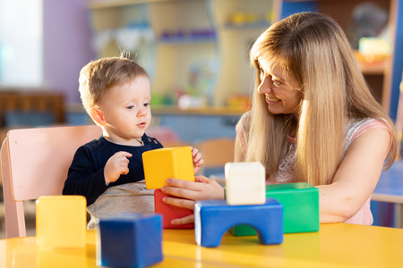 Child toddler boy together with mother playing educational toys at sunny day in nursery Stock Photo