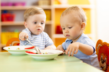 babies children boys eating healthy food in nursery or kindergarten