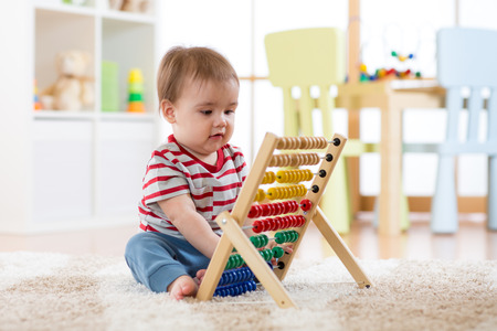 Baby boy playing with an abacus learning to count