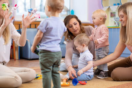 Friends with children sitting and playing on the floor in nursery room