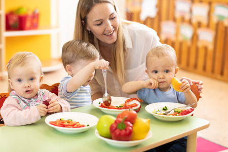 little kids with mentor eat vegetables in nursery