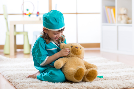 little child girl with doctor clothes plays with teddy bear