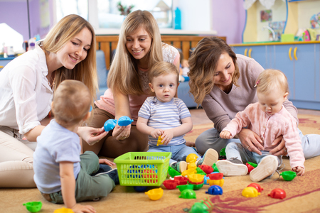 Group of mothers with babies toddlers at playgroup Stockfoto
