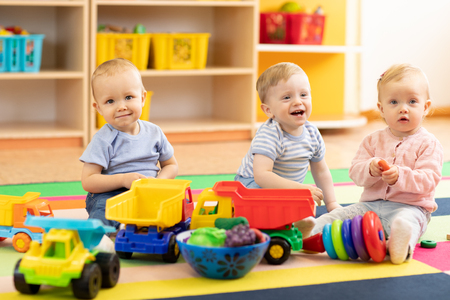 Group of babies is playing on floor in nursery or creche. Children in the day care center. Fun in the children's playroom