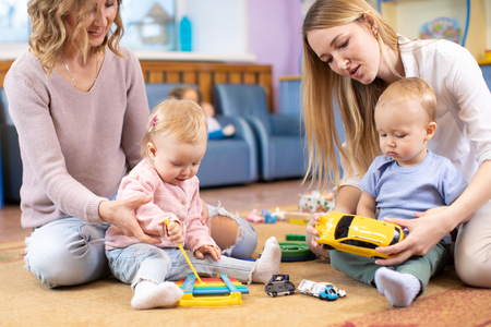 Babies play and their mothers communicate in playroom in daycare 版權商用圖片