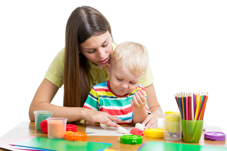 Young woman playing with her boy with plasticine on white background