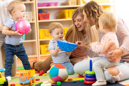 Group of moms with their babies in nursery