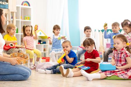 Kinder, die verschiedene Musikspielzeuge spielen. Musikalische Früherziehung im Kindergarten