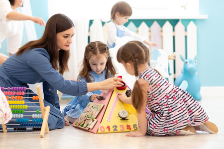 Cute kids playing with busy board in kindergarten. Childrens educational toys. Wooden game board.