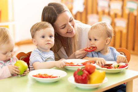 Babies eating healthy food in kindergarten