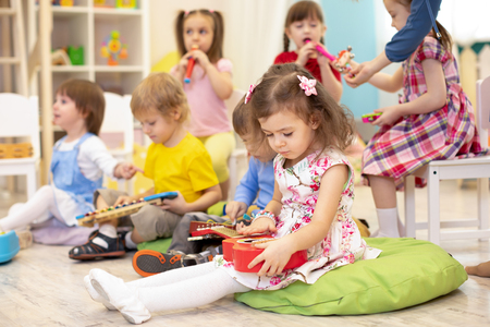 Children learning musical instruments on lesson in kindergarten