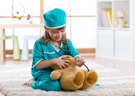 Kid weared doctor clothes playing with teddy bear