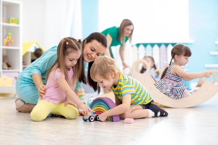 Preschool children playing with teacher in kindergarten Standard-Bild