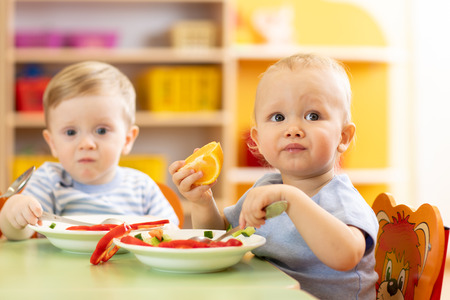 Babies have a lunch in nursery Banque d'images - 116466476