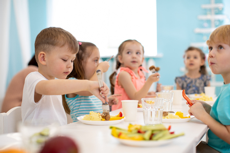Kids enjoying healthy lunch in kindergarten Standard-Bild