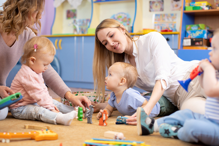 babies playing with toys sitting on floor in nursery