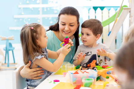 Teacher with children working with plasticine at kindergarten or playschool Foto de archivo