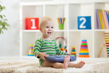 Happy kid boy playing piano toy in nursery room Stockfoto