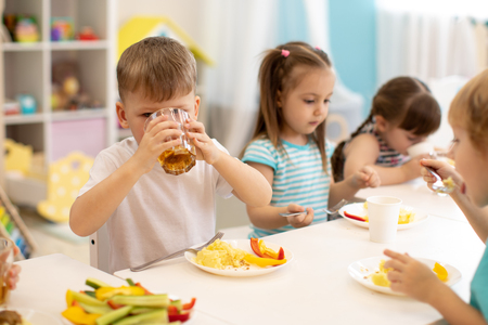 Lunch in daycare. Kid boy drinking juice during dinner in kindergarten