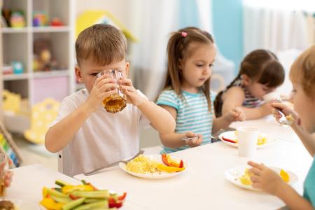 Mittagessen in der Kita. Kinderjunge trinkt Saft während des Abendessens im Kindergarten