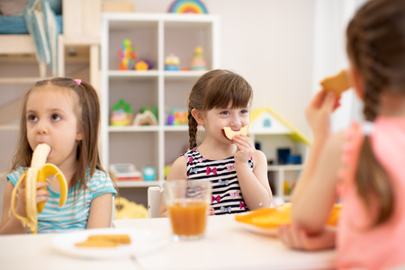 Funny children girls eating healthy food. Kids lunch at daycare or kindergarten.