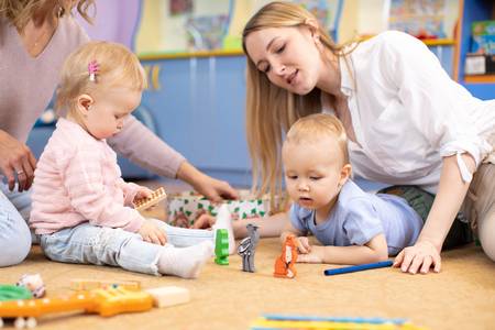 Nursery babies with moms or teachers playing with wooden educational toys sitting on a floor indoor