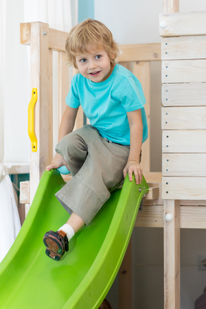 Kid boy playing fun in the playroom, coming down from the green hill Stockfoto