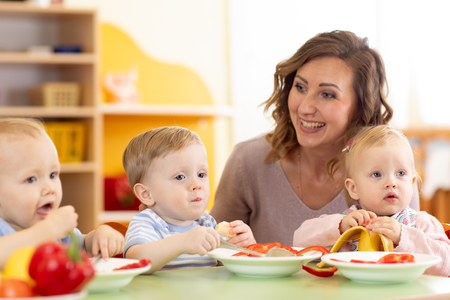 Group of nursery babies eating healthy food lunch break together with kindergartener