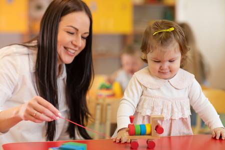 Teacher and baby one year ago playing logical toys in nursery Stock Photo