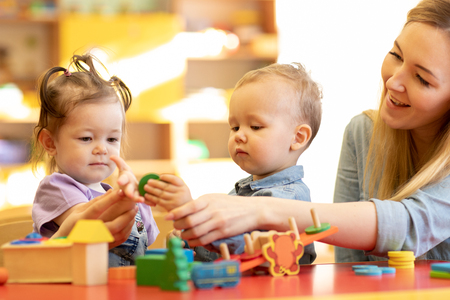 Nursery babies playing with teacher in the classroom Standard-Bild - 118977981