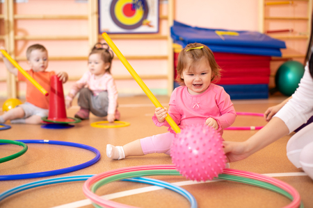 Happy sporty children in nursery gym