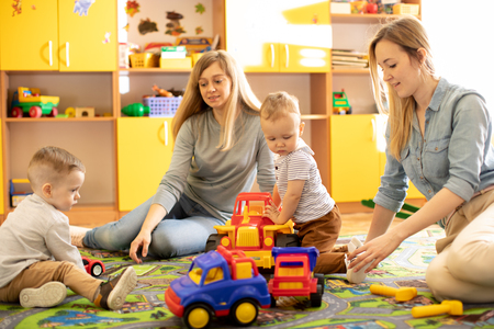 Mothers with kids play toy cars in nursery