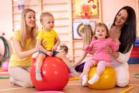 Mothers with happy babies doing exercises with gymnastic ball in gym. Concept of caring for the babys health.