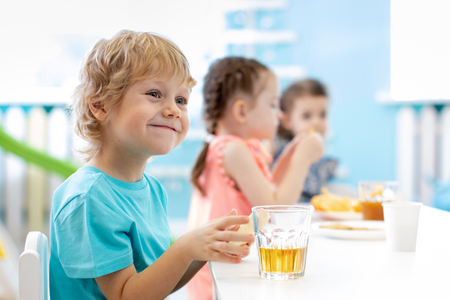 Children boy and girls at daycare lunch table
