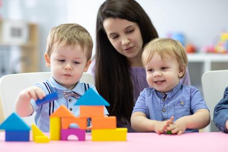 Maestra de preescolar y niños lindos juegan en el jardín de infantes