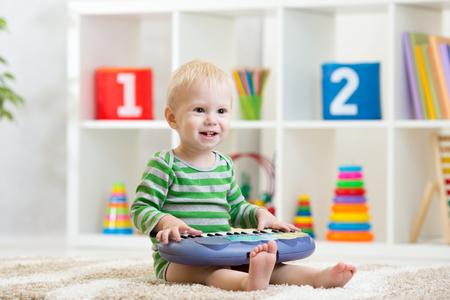 Jongen die speelgoedpiano speelt in de kinderkamer Stockfoto