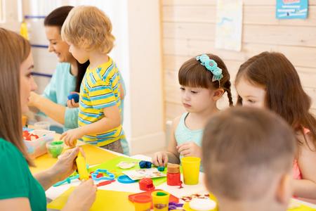 Kindergarten teacher teaches group of children modeling clay