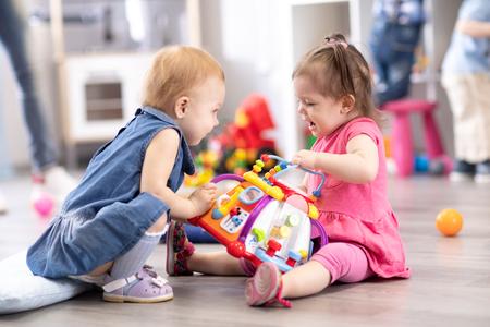 Conflit sur le terrain de jeu. Deux enfants se disputent un jouet à la maternelle