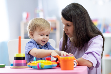 Cute woman with child playing with plastic blocks at home or kindergarten