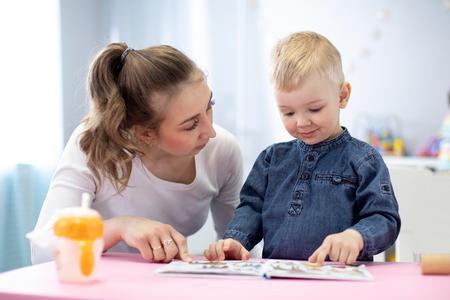 Mère ou baby-sitter lisant un livre à un enfant. À l'intérieur Banque d'images