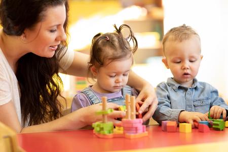Kinderen spelen met vormen en kleurrijke houten puzzel in een montessoriklaslokaal