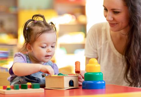 Niño de guardería jugando juguetes de desarrollo con la madre o el maestro