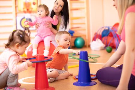 Kleine kinderen met hun moeders in de kleuterschool Stockfoto