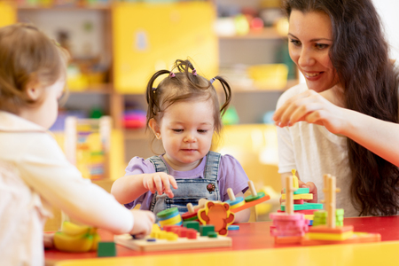 Kids play with shapes and colorful wooden puzzle in a montessori classroom Stock fotó