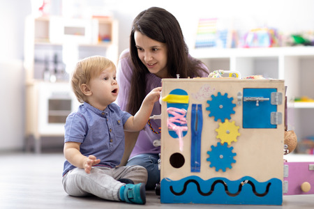 Child with teacher playing educational toys, stacking and arranging colorful pieces. Learning through experience concept, gross and fine motor skills.
