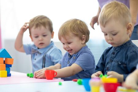 Kindergartenkinder, die im Kindergarten oder in der Spielschule mit Spielton spielen