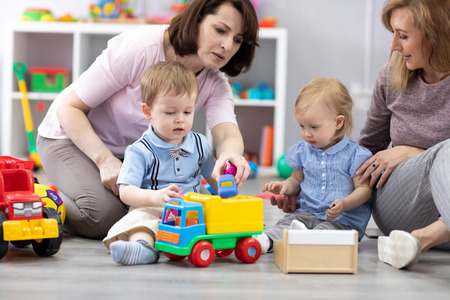 Nursery kids playing with toys. Moms communicate and watch over their children