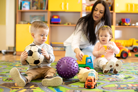 Nursery teacher looking after children in kindergarten. Little kids toddlers play together with developmental toys. Stok Fotoğraf