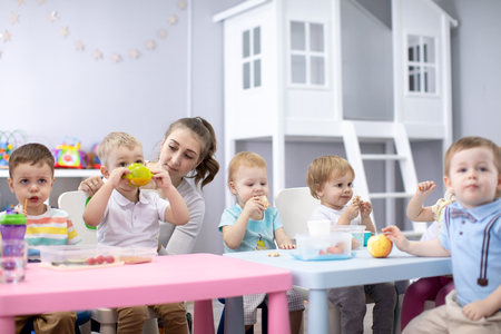 Group of kids having lunch in nursery or daycare centre